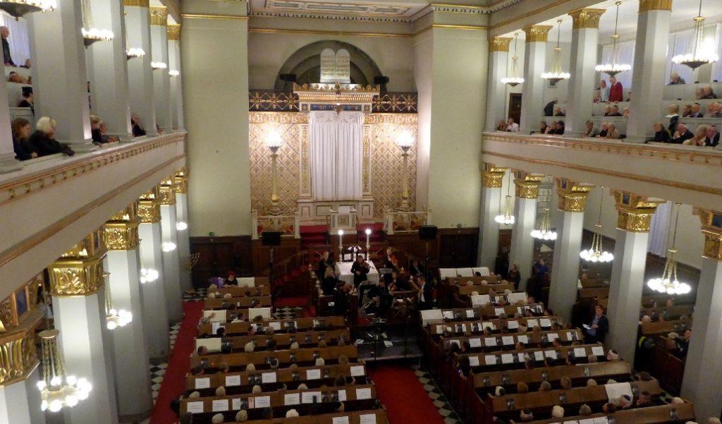 Publikum og musikere i en fyldt synagoge i fugleperspektiv