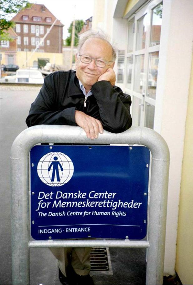 Isi Foighel ved skiltet for Det Danske Center for menneskerettigheder